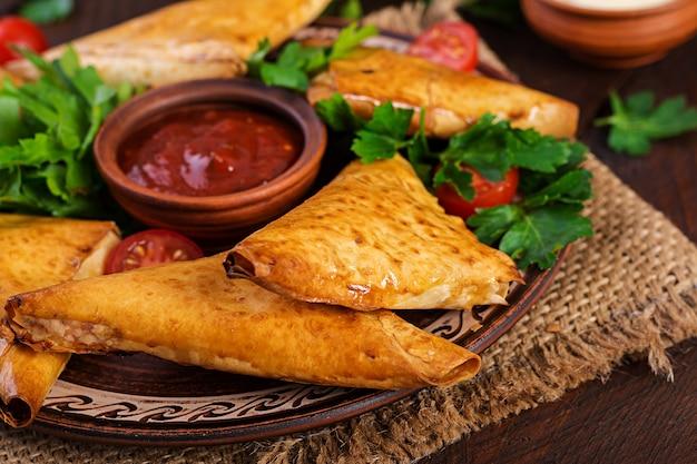 Azjatyckie jedzenie. samsa (samosas) z filetem z kurczaka i serem.