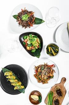 Azjatyckie jedzenie serwowane na białym stole. zestaw dań kuchni chińskiej i wietnamskiej. szare tło. widok z góry