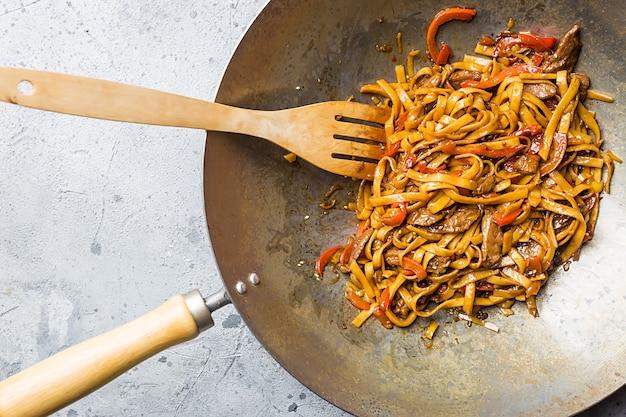 Azjatyckie jedzenie, smażony makaron udon z mięsem i warzywami na patelni wok na szarej kamiennej powierzchni, widok z góry