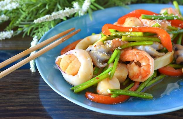 Azjatyckie jedzenie z owocami morza, warzywami w sosie sojowym na talerzu
