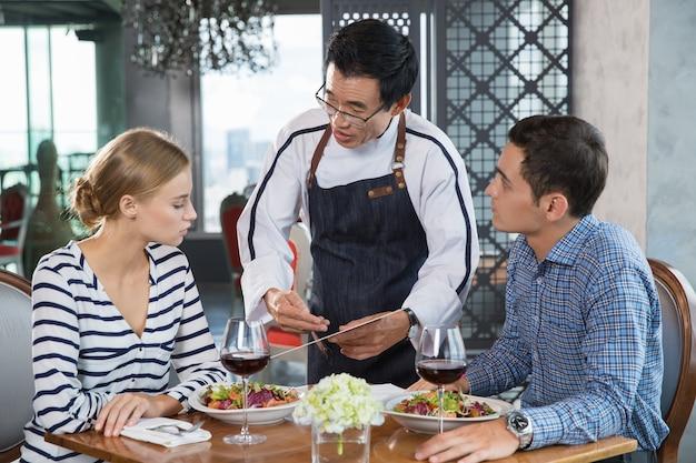 Azjatyckie kelner making zalecenie dla młodej pary
