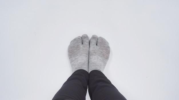 Azjatyckie kobiece stopy z japońską skarpetą na białym tle.