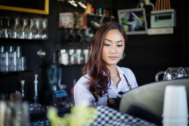 Azjatyckie kobiety barista uśmiecha się kawową maszynę w sklep z kawą i używa - kontuar - kobieta pracująca małego biznesu właściciela jedzenia i napoju kawiarni pojęcie