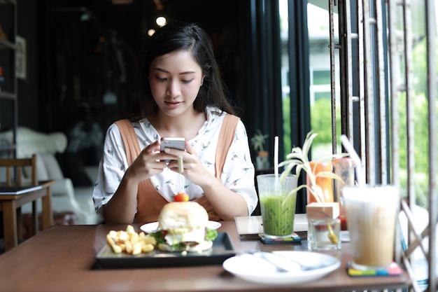 Azjatyckie kobiety bierze fotografię hamburgery i cieszyli się jedzeniem przy kawą i restauracją dalej relaksują czas