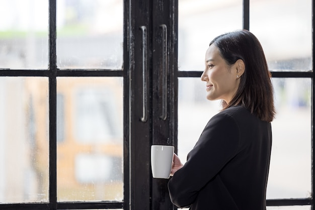 Azjatyckie kobiety biznesu trzymające filiżankę kawy i stojące przy oknie biura w czasie przerwy