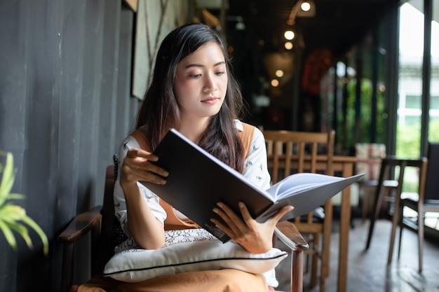 Azjatyckie kobiety czyta, uśmiechnięty i szczęśliwy relaksować w sklep z kawą po pracować w pomyślnym biurze.