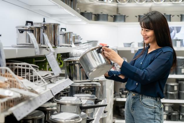 Azjatyckie kobiety decydują się na zakup nowych naczyń kuchennych w centrum handlowym. zakupy artykułów spożywczych i artykułów gospodarstwa domowego.