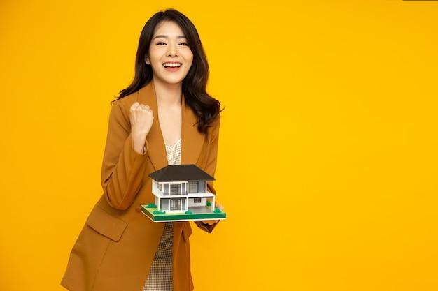 Azjatyckie kobiety gospodarstwa model próbki domu na białym tle na żółtej ścianie.