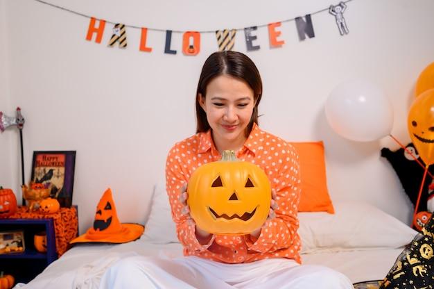 Azjatyckie kobiety gospodarstwa twarz dyni na halloween festiwal w domu. dekoracja sypialni na uroczystość dla dzieci i rodzin jesienią i jesienią.