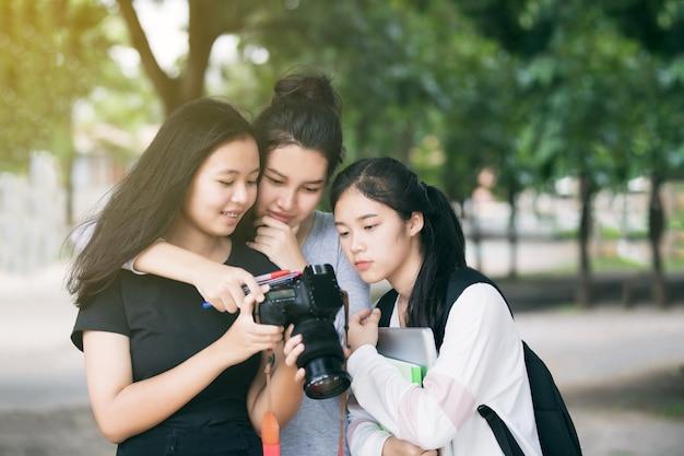 Azjatyckie kobiety grupują turystów patrzeje kamera monitor sprawdza obrazki brać