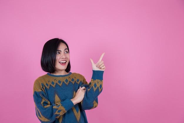 Azjatyckie kobiety i przestrzeń życiowa, która jest wskazana na różowym tle palca.