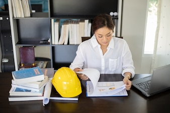 Azjatyckie kobiety inżynieria sprawdza i pracuje i trzyma projekty przy biurem