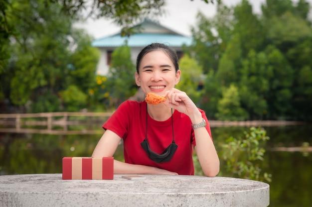 Azjatyckie kobiety jedzą skrzydło kurczaka, siedząc na stole