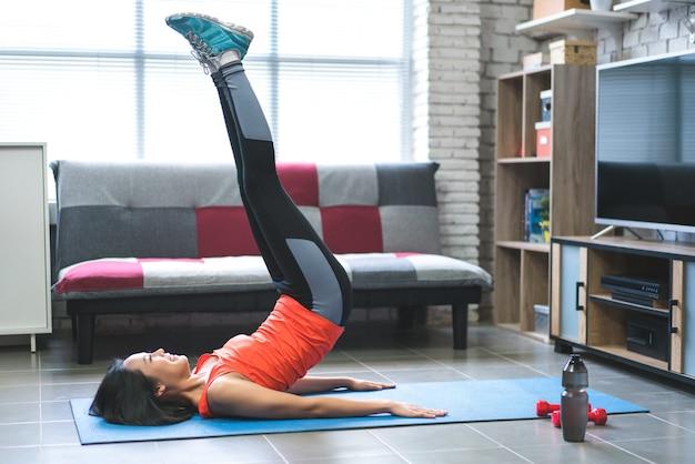 Azjatyckie kobiety jest szczęśliwa, aby ćwiczyć w domu.