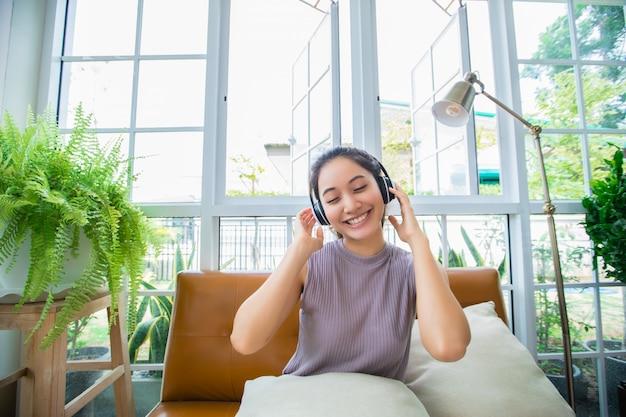 Azjatyckie kobiety jest ubranym hełmofony i używa laptop i cyfrową pastylkę dla słuchać muzyka i śpiewać w relaksującym dniu w domu
