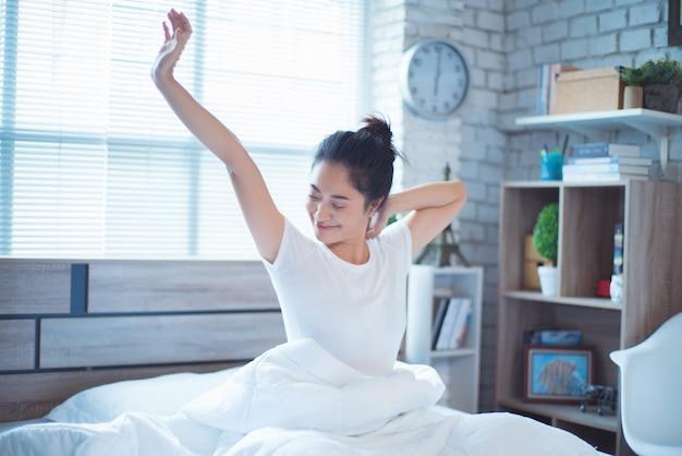 Azjatyckie kobiety jest w łóżku i budziła się rano. czuła się bardzo odświeżona.