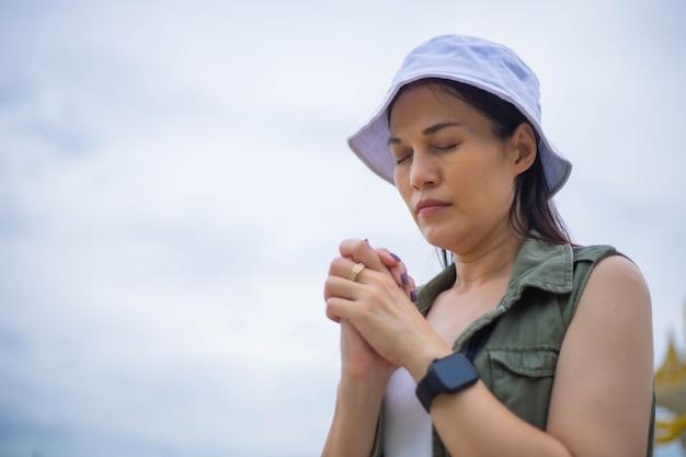 Azjatyckie kobiety modląc się rano na zewnątrz, ręce złożone w koncepcji modlitwy o wiarę, duchowość i religię, koncepcja usług kościoła online.