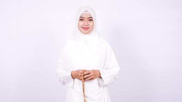 Azjatyckie kobiety muzułmańskie modlą się na białej ścianie