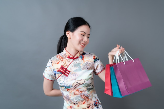Azjatyckie kobiety nosić chiński tradycyjny strój z ręki trzymającej torbę na zakupy na szarej powierzchni