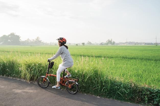 Azjatyckie kobiety noszą kaski do jazdy na składanych rowerach na polach ryżowych