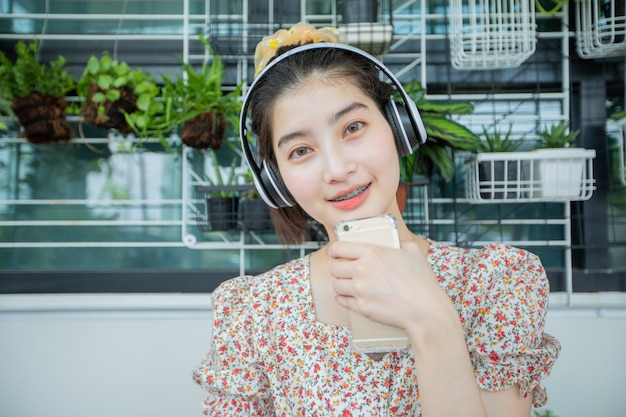 Azjatyckie kobiety noszące słuchawki i używające telefonu komórkowego i cyfrowego tabletu do słuchania muzyki i śpiewania podczas relaksującego dnia w domu