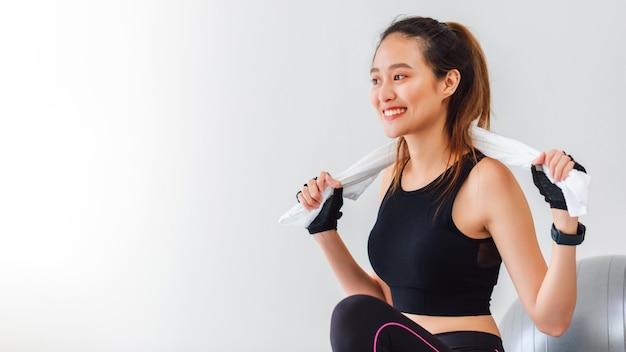 Azjatyckie kobiety odpoczynek po zabawie jogi i ćwiczeń w domu w tle z miejsca na kopię.