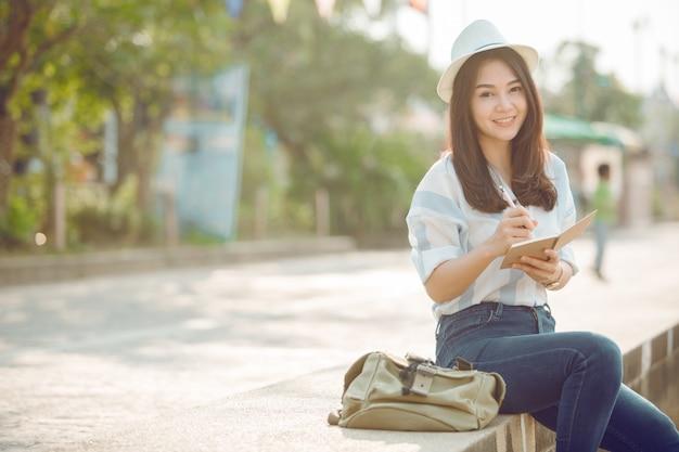 Azjatyckie kobiety podróżują relaks w holiday.sit napisać notatkę.