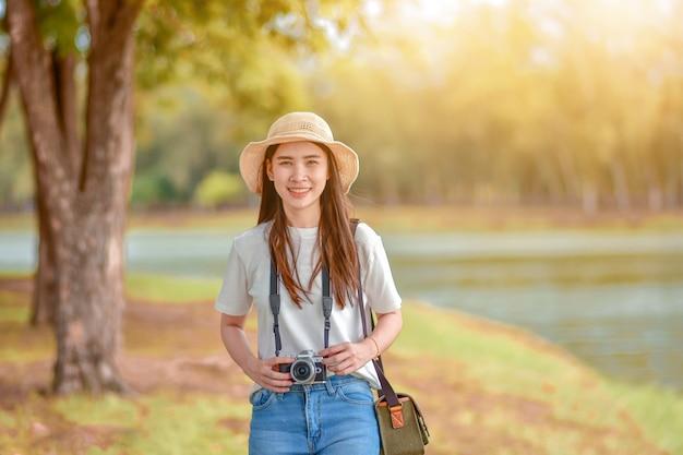 Azjatyckie kobiety podróżują w naturze z kamerą bierze fotografię