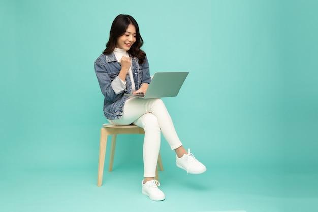 Azjatyckie kobiety posiadające komputer przenośny i siedząc na krześle na białym tle na zielonym tle.