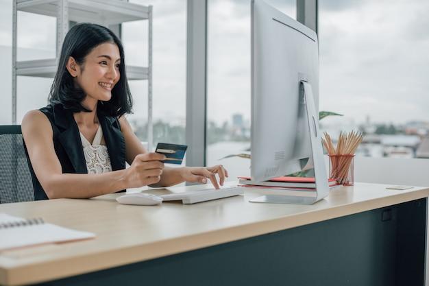 Azjatyckie kobiety posiadania karty kredytowej i przy użyciu komputera stacjonarnego z zakupów online i pracy z koncepcji domu.