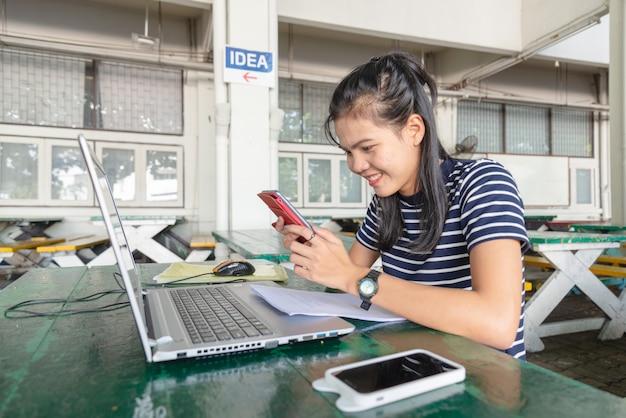 Azjatyckie kobiety pracowały z telefonem komórkowym i notatnikiem na stole w uniwersyteckim terenie. wygląda na szczęśliwą z pracy. koncepcja uzależnionego od mediów społecznościowych.