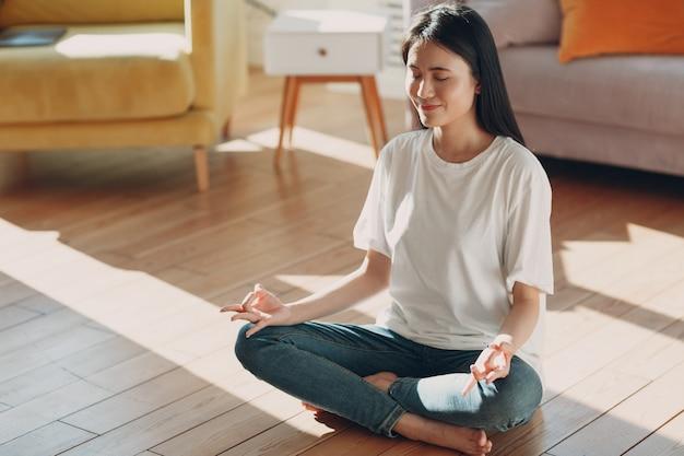 Azjatyckie kobiety robi joga i zen jak medytacja w pozycji lotosu w casual w krytym salonie z naturalnym światłem słonecznym.