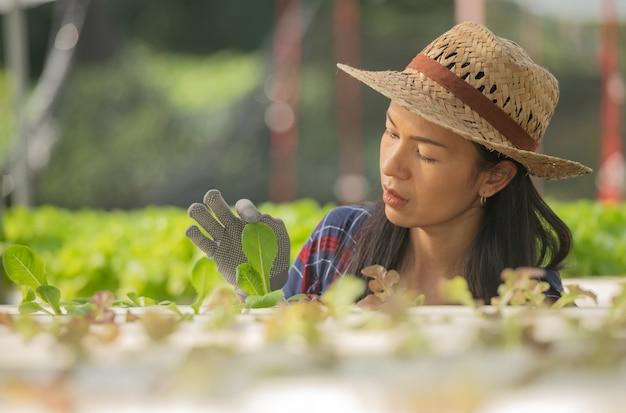 Azjatyckie kobiety rolnicy pracujący w uprawie hydroponicznej warzyw ze szczęścia. portret kobiety rolnik sprawdzanie jakości zielonej sałaty warzywnej z uśmiechem w gospodarstwie zielonym domu.