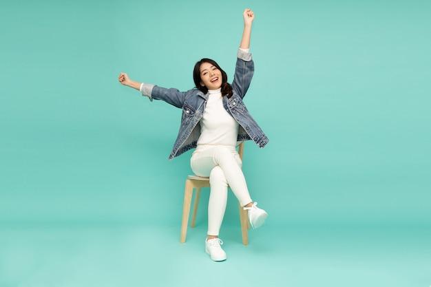 Azjatyckie kobiety siedzącej na białym nowoczesne krzesło szczęścia na białym tle na zielonej ścianie.