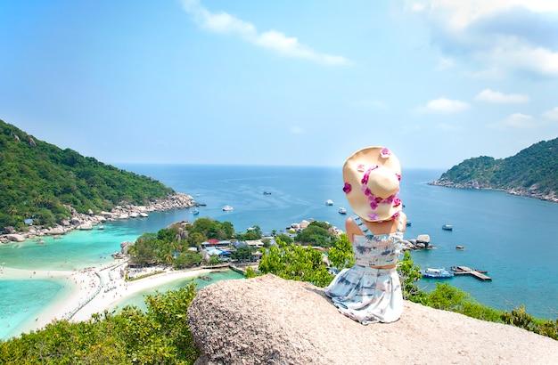 Azjatyckie kobiety siedzącej na kamień w amazing punktu widzenia w nangyuan island.