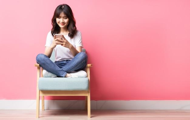 Azjatyckie kobiety siedzącej na kanapie przy użyciu swojego telefonu ze szczęśliwym wyrazem twarzy