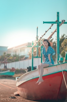 Azjatyckie kobiety siedzącej na plaży łodzi w mieście