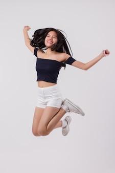 Azjatyckie kobiety skoki. studio na białym tle portret szczęśliwej, uśmiechniętej, podekscytowanej kobiety skaczącej, skaczącej, skaczącej z radości. młoda dorosła azjatycka kobieta modelka