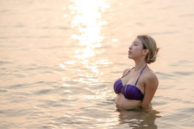 Azjatyckie kobiety sobie fioletowy strój kąpielowy syrenka siedzi w wodzie oceanu przy piaszczystej plaży.