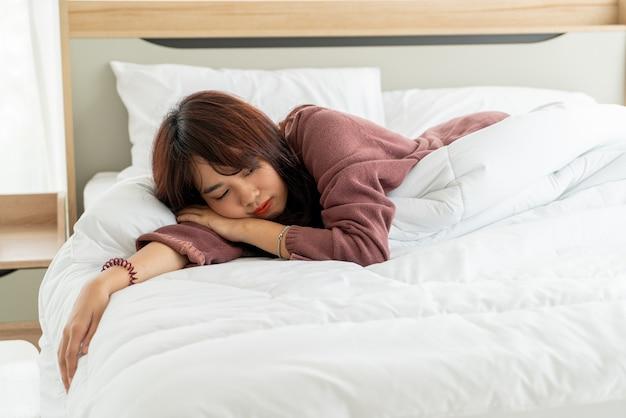 Azjatyckie kobiety śpi na łóżku w ranku