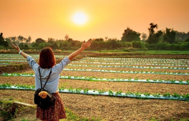 Azjatyckie kobiety stoi przed zachodem słońca na uprawie ziemi na słabym oświetleniu.
