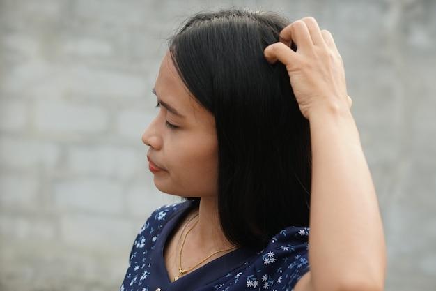 Azjatyckie kobiety swędzący łupież skóry głowy