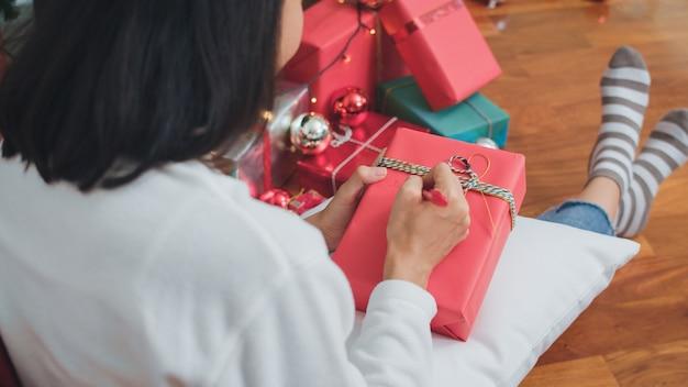 Azjatyckie kobiety świętują święta bożego narodzenia. kobieca nastoletnia odzież sweter i czapka świętego mikołaja relaksują się, piszą życzenia na prezent w pobliżu choinki, ciesz się świętami zimowymi boże narodzenie razem w salonie w domu.