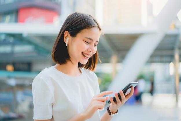 Azjatyckie kobiety szczęśliwe uśmiechnięte słuchają muzyki z białych słuchawek.