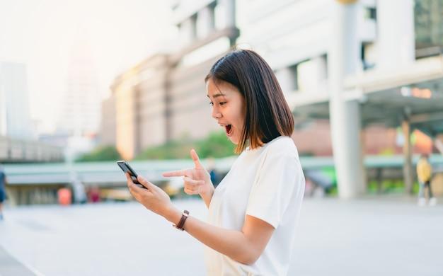 Azjatyckie kobiety szczęśliwy ono uśmiecha się i trzyma mądrze telefon z zadziwiający dla sukcesu.