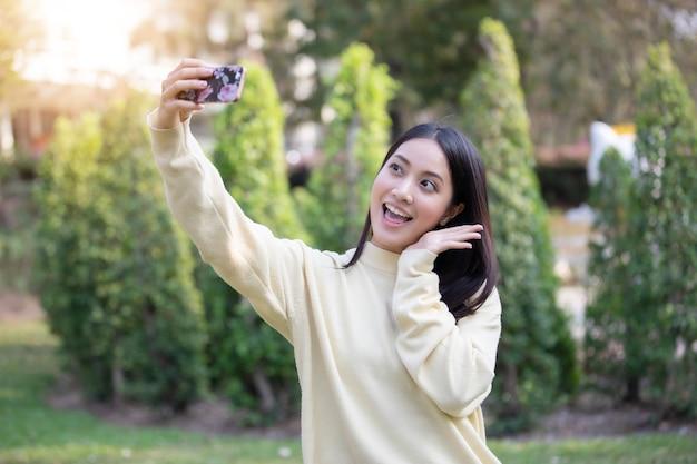 Azjatyckie kobiety szczęśliwy uśmiech bierze fotografie i selfie na relaksującym czasie
