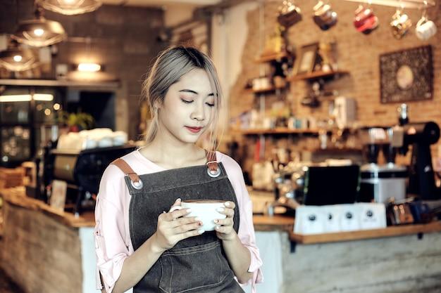 Azjatyckie kobiety trzyma filiżankę kawy w kawiarni
