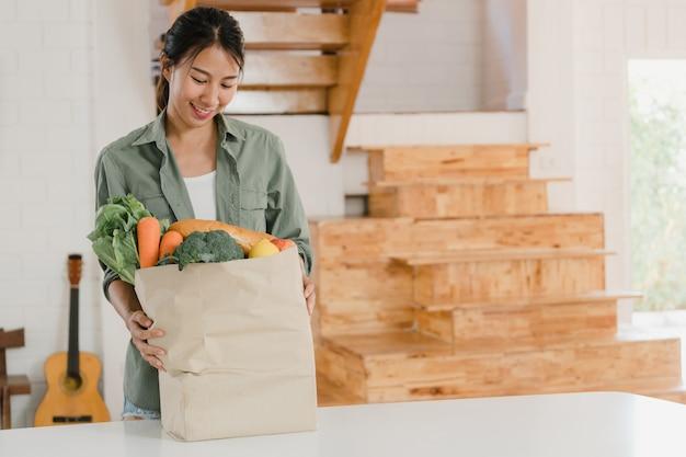 Azjatyckie kobiety trzyma sklep spożywczego robi zakupy papierowe torby przy hom