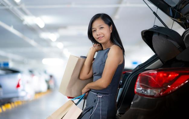 Azjatyckie kobiety trzymają torby na zakupy z tyłu samochodu