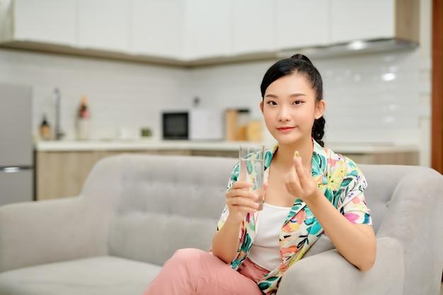 Azjatyckie kobiety trzymającej pigułkę i szklankę wody siedząc na kanapie.